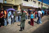 """Los presidentes de Venezuela y Colombia acordaron abrir """"de manera progresiva"""" su frontera, después de que Caracas decidió su cierre como parte de una medida para frenar el flujo de billetes de 100 bolívares, el de mayor denominación y aún vigente tras un nuevo cono monetario. En la imagen, un soldado venezolano controla una fila de gente en Ciudad Bolivar, Venezuela, el 19 de diciembre de 2016.  REUTERS/William Urdaneta"""