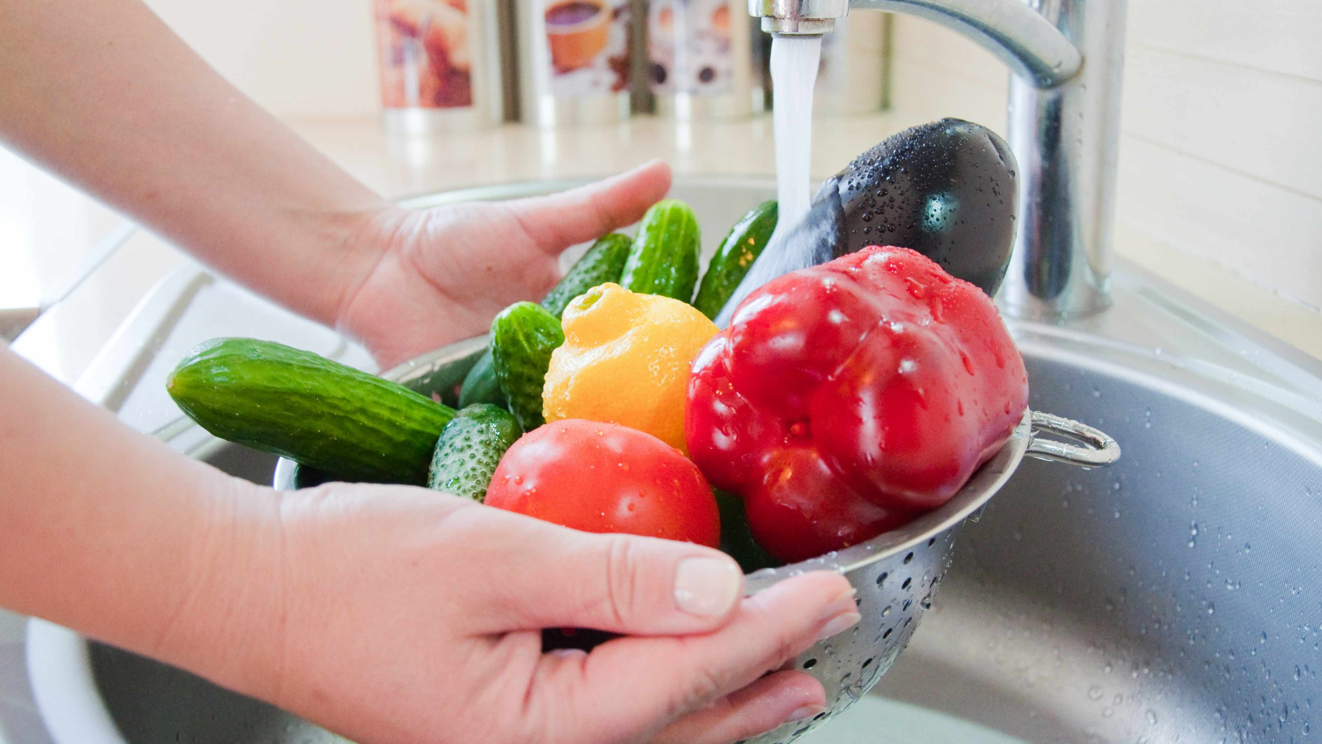 a-person-washing-vegetables-and-fruits-under-kitchen-water-faucet-16x9