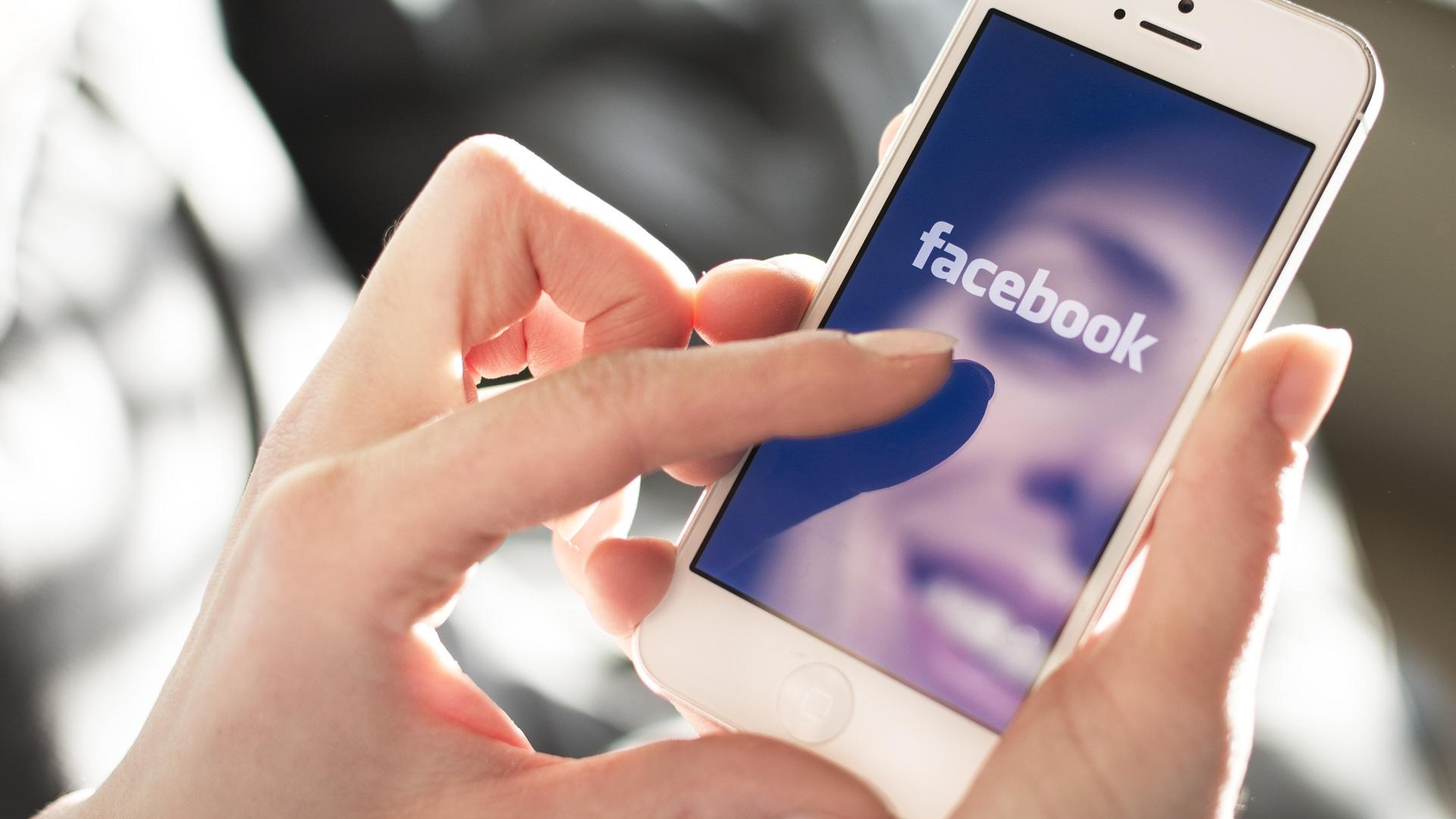 manos-sosteniendo-celular-y-entrando-a-facebook